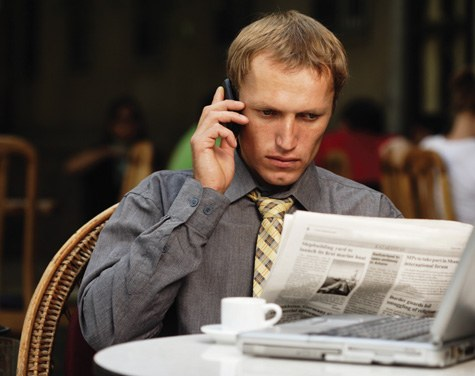 A man on a cell phone reading the newspaper at a table.