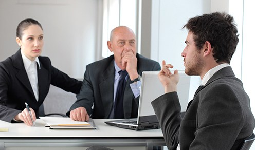Stock image of a man being interviewed by a woman and another man while sitting at a table in an office.