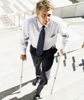 Stock image of a man walking up steps with the assistance of crutches. © Thinkstock.com