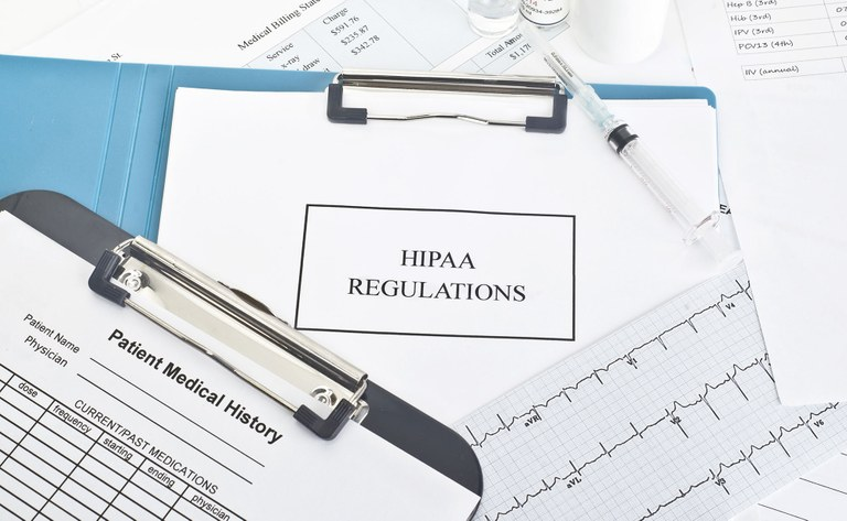 A stock image of a patient medical history form and HIPPA regulations form.