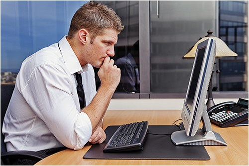 Stock image of an investigator working on a desktop computer in an office.