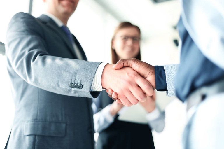 Stock image of two men engaged in a hand shake.