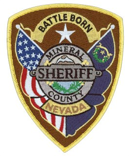 "Nevada's official nickname, the ""Silver State,"" and its unofficial nicknames the ""Battle Born State"" and the ""Sagebrush State"" are on the patch of the Mineral County, Nevada, Sheriff's Office. The central emblem contains the sagebrush, the state flower, on the bottom half, and the famous landmark Mt. Grant on the top; a silver circle encases the emblem, which honors Nevada's rich history with silver mining. The words ""Battle Born"" at the top recall Nevada's entry into statehood during the Civil War."