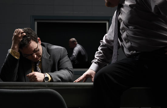 A police detective speaks with a suspect in an interrogation room.