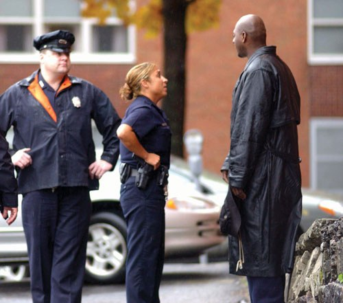 Police officers speak to a person at a crime scene.