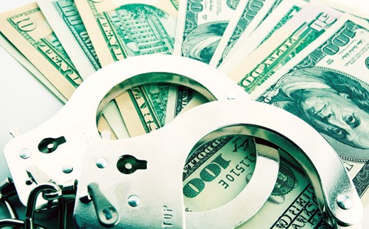 Stock image of a pair of handcuffs resting on a series of bills of various denominations. © Photos.com