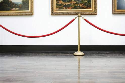 Three paintings behind a rope at a museum. © Thinkstock.com