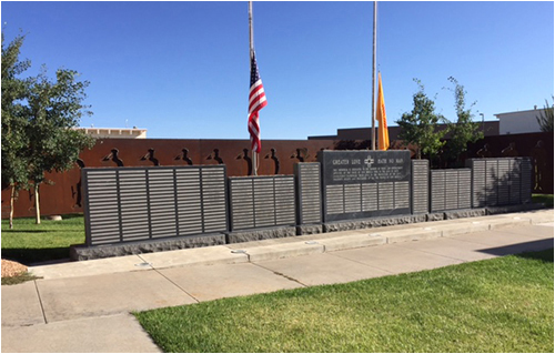 The New Mexico Law Enforcement Memorial sits in a beautiful courtyard on the grounds of the state law enforcement academy. Steel cut-out silhouettes of 28 officers guard and salute the monument's wall, which features the names of personnel—currently 204—lost in the line of duty. United States and New Mexico flags fly at half-staff.