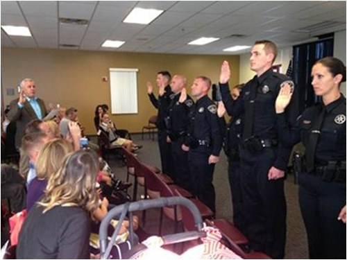 A group of police officers being sworn in as family and friends look on.