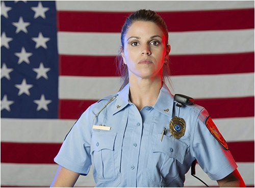 Stock image of a female police officer with an American flag in the background.