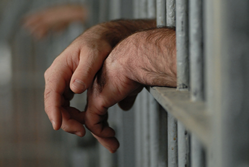 Hands Sticking Out from Behind Prison Bars