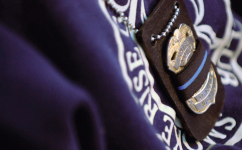 A badge is depicted with a mourning strip across it.