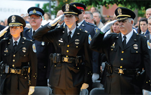 Police personnel attend a vigil in honor of fallen officers.