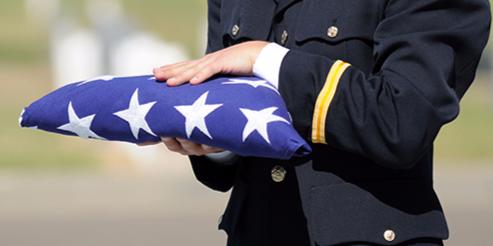 Officer Holding Folded American Flag