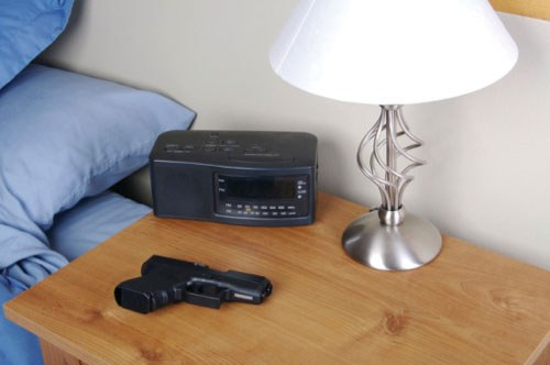 A firearm is pictured on a night-table adjacent to a clock-radio.