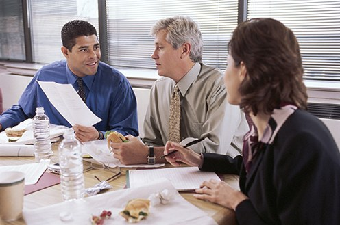 Stock image of three people sitting at a table eating lunch at work.