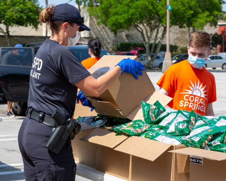 A stock image of a police officer assisting at a food distribution site.