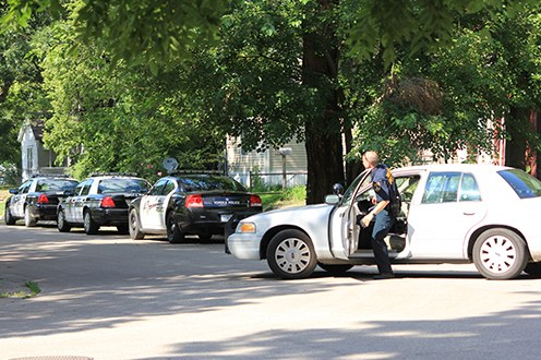 A police officer gets out of his vehicle in a neighborhood with three other police cars parked nearby.