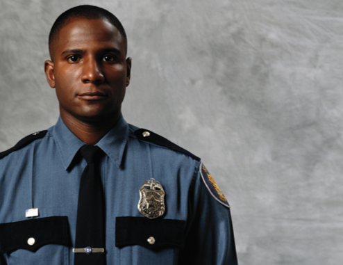 A police officer in uniform in front of a gray backdrop.