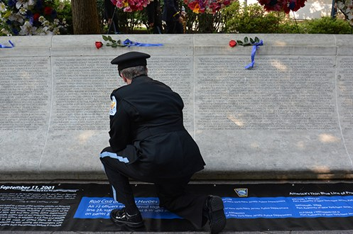 A police officer in uniform kneels down in front of a section of the National Law Enforcement Officers Memorial in Washington, D.C.