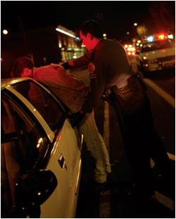 A police arrests a man on his squad car. ©Thinkstock.com.