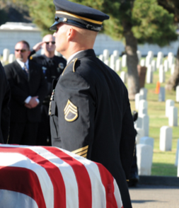 A police officer stands at attention at a law enforcement funeral. © shutterstock.com.