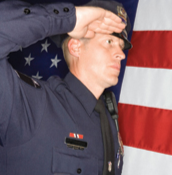 A police officer stands at attention, saluting. © Photos.com