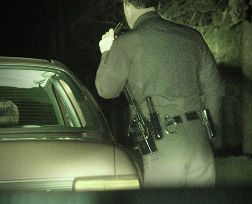 A police officer shines a flashlight into a car with a person in the backseat at night.