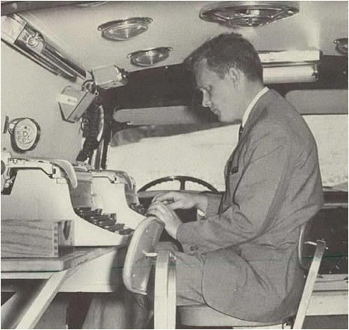 Archive photo of a law enforcement officer using a typewriter in a mobile command vehicle from 1964