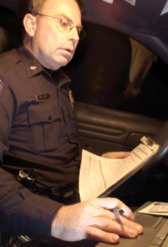 An officer enters information into his vehicle's portable computer system.