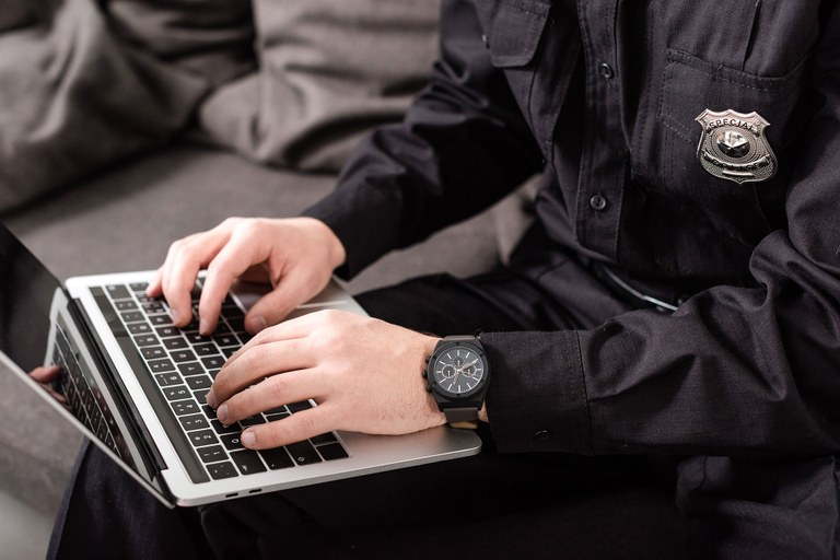 A stock image of a male officer working on a laptop.
