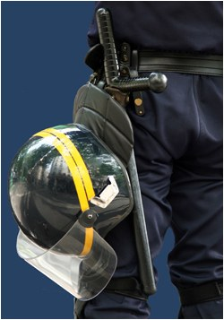 A police officer's belt with a night stick and helmet.