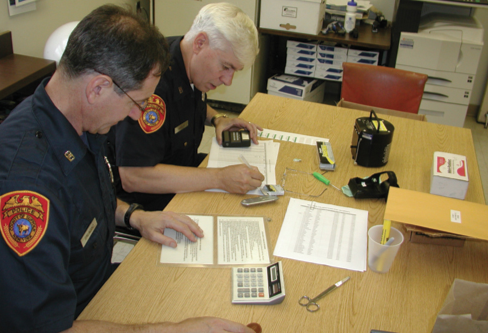 Suffolk County (New York) police personnel performing an annual calibration on some of the department's personal radiation detectors (PRDs).
