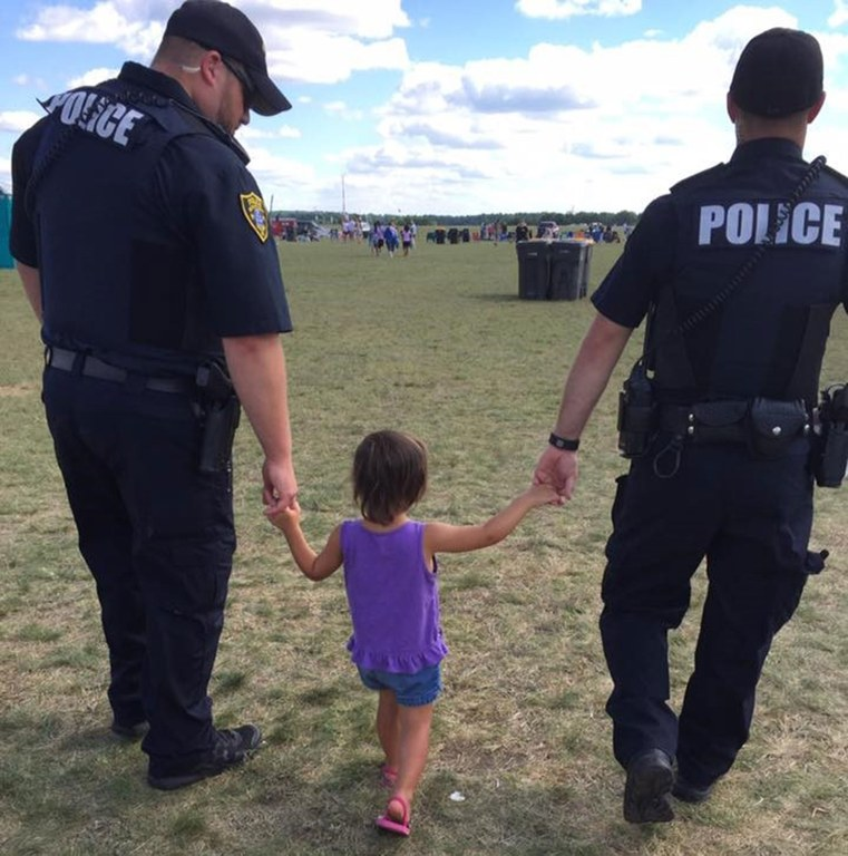 Two officers holding the hands of a lost, young girl.