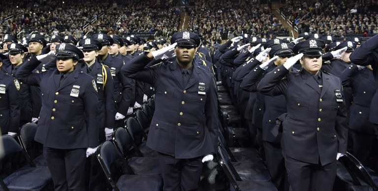 Stock image of police officers saluting during graduation ceremony.