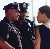 Two law enforcement professionals talk with a teenager.
