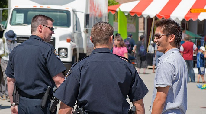A stock image of two officers talking to a young adult male at a festival.