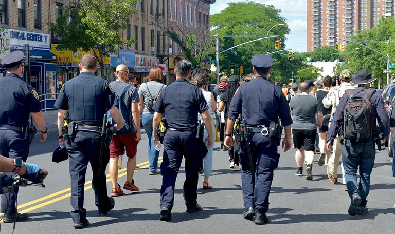 A stock image of several police officers marching with people from their community.