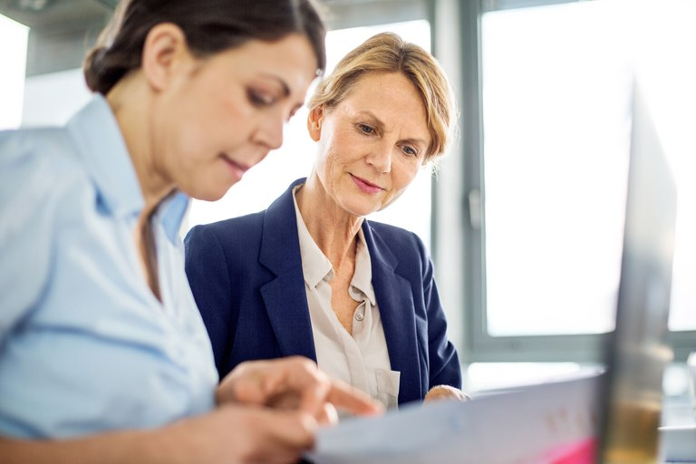 A stock image of an older business woman working with a younger employee.