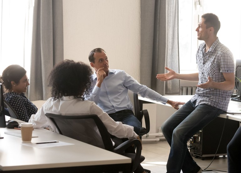 A stock photo of a group of adults having a discussion.