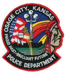 The patch of the Osage City, Kansas, Police Department prominently references the city's proud past and brilliant future. One of the city's famous 6th Street light poles is shown in the center, followed below by strands of wheat, a well-known staple in Kansas. The background depicts a flowing American flag symbolizing national pride, as well as the city skyline with its large water tower. To the right is a representation of the Osage Indian, after which the city is named.