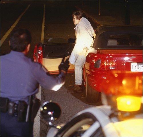 The officer executes a traffic stop, and immediately a male subject exits the vehicle and attempts to walk away. The officer detains the subject, asks for identification, and conducts a frisk search.