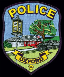 "The patch of the Oxford, Pennsylvania, Police Department depicts historical landmarks located throughout Oxford. The red building represents the train station that housed the police department from the 1950s until 2009. The tree recalls the 300-year old ""William Penn Oak,"" located in the center of town. The foreground includes the town clock from Oxford's business district; its hands remain fixed at 9:11 as a tribute to all those who lost their lives on September 11, 2001."