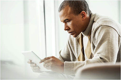Father Looking at Computer Tablet (Stock Image)