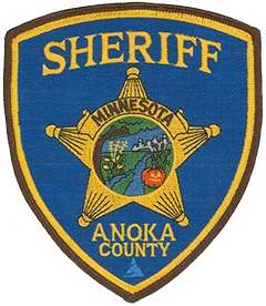 "The patch of the Anoka County, Minnesota, Sheriff's Office represents the unique qualities of the area it serves. The oak tree on the left symbolizes the county's suburban development and pleasant communities, while the skyline signifies its relationship with nearby Minneapolis-St. Paul. The two rivers—the Rum and Mississippi—denote the city of Anoka, founded in 1844 at the site of their confluence. The jack-o-lantern also represents the city, which is the self-proclaimed ""Halloween Capital of the World"" because it hosted one of the first Halloween parades in the United States in 1920. The cattails and corn on either side of the two rivers symbolize the undeveloped, recreational, and agricultural areas of Anoka County."
