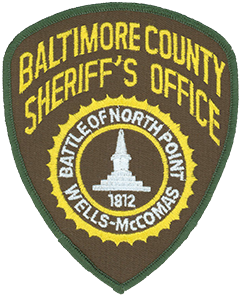 The patch of the Baltimore County, Maryland, Sheriff's Office depicts the Wells and McComas Monument, a 21-foot obelisk built in 1873 to honor two members of the Maryland State Militia—Daniel Wells and Henry McComas—who defended Baltimore in the War of 1812. According to legend the two teenage militiamen shot and killed Major General Robert Ross, commanding officer of the British troops near the city, during the Battle of North Point on September 12, 1814. Wells and McComas both fell in battle shortly afterward and are interred beneath the monument that honors them.