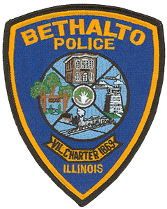 The village of Bethalto, Illinois, is located in the greater St. Louis, Missouri, metropolitan area and was incorporated under a special charter in 1869. This charter date is shown below the village seal on the service patch of the Bethalto Police Department. Pictured clockwise in the seal are the old Village Hall—built in 1874—and the control tower of St. Louis Regional Airport, located in Bethalto. A coal train symbolizes the village's coal mining history, and the Bethalto Arboretum is depicted via the trees and walkway. The hand at the center of the seal represents the Bethalto Spirit organization, a volunteer group working for the betterment of the village.
