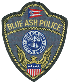 "The city of Blue Ash, Ohio, is a suburb of Cincinnati and first was settled in 1791. The service patch of the Blue Ash Police Department depicts the Ohio state flag at the top, the city seal in the center, and an American bald eagle with the Union Shield at the bottom. Inside the blue and white city seal is an adult and child walking under a blue ash tree with a building in the distance. The motto of Blue Ash, ""City of Choice,"" is featured on the seal's border. The patch's rope edging, department name, and eagle are stitched in either metallic silver or gold thread depending on the rank of the officer—investigators and patrol officers wear the silver-lined patch, while sergeants and above sport the gold-lined version."