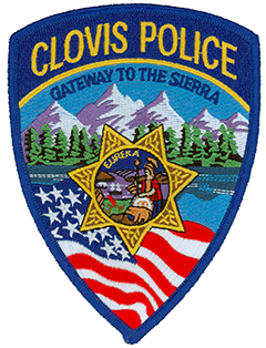 Since its incorporation in 1912, Clovis, California, has been known as the Gateway to the Sierra due to its location at the base of the Sierra Nevada mountain range in central California. The range proudly serves as the backdrop to the Clovis Police Department patch and is depicted above acres of lush forest. Clovis began in 1891 as a freight stop for the railroad and grew to include a lumber mill with a 42-mile-long log flume. The center of the patch depicts the Great Seal of California while a flowing American flag is shown in the foreground.