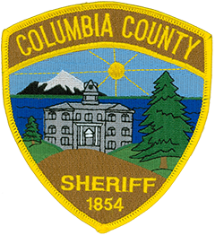 Columbia County, Oregon, was founded in 1854 and is named after the Columbia River, which forms the county's northern and eastern borders. A scene from St. Helens, the county seat, is featured on the patch of the Columbia County Sheriff's Department. The center of the patch depicts the county courthouse, which dates back to 1906. The dark-blue background represents the river, and the green horizontal line is the shore of neighboring Washington state, prominently depicting the Mount St. Helens volcano. The sun rises to the east of the courthouse, as shown, and the trees and green and brown areas represent the timber and agricultural resources of the county.